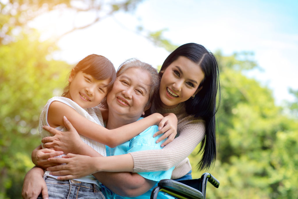 Grandmother, mother, and daughter smiling
